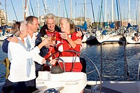 Two mature couples standing at helm of yacht moored at harbour jetty, raising celebratory toast with wine glasses, smiling