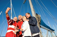 Two mature couples standing on deck of yacht moored at harbour jetty, posing for group photograph, senior man taking self-portrait with digital camera...