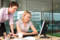 Two businesswomen working at desk in office, blonde using flat screen computer, brunette looking on, smiling