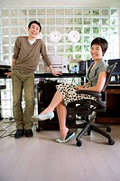 Young man standing by young woman sitting by desk in office, smiling, portrait