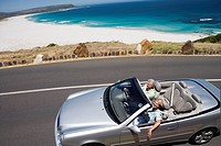 South Africa, Cape Town, senior couple driving on silver convertible car by sea, elevated view