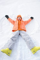 Girl 6-8 lying in snow with arms and legs outstretched, smiling, protrait, elevated view