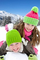Brother and sister 6-8 wearing woolen hats, lying in snow, smiling, portrait, close-up