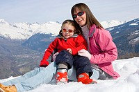 Mother and daughter 6-8 sitting together in snow field, wearing sunglasses, smiling, portrait, mountain range in background