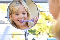 Girl 6-8 brushing teeth in bathroom, looking at reflection in mirror
