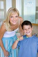 Mother and son 6-8 holding toothbrushes in bathroom, smiling, portrait