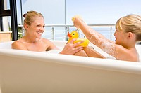 Mother and daughter 6-8 in bath outdoors, woman with rubber duck, smiling at each other