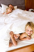 Couple with son and daughter 6-8 lying in bed, children smiling in foreground, elevated view