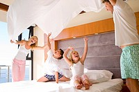 Parents raising bed sheet in air above son and daughter 6-8 in bedroom