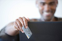 Young man credit card by laptop, smiling, portrait focus on credit card
