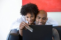 Young woman embracing young man holding credit card by laptop, smiling