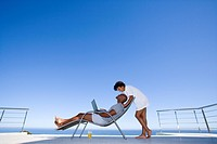 Young woman standing by young man sitting with laptop on deck chair by sea, side view