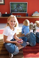 Boy and girl 6-8 on rug in front of television, portrait of girl smiling and using mp3 player
