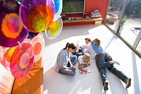 Couple with son and daughter 6-8 on floor by television in living room, elevated view