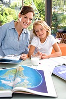 Mother helping daughter 6-8 with geography homework, smiling, portrait, world atlas in foreground