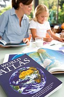 Mother helping daughter 6-8 with geography homework, world atlas in foreground