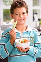 Boy 6-8 holding up piece of cucumber from bowl, smiling, portrait