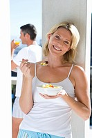 Young woman eating fruit salad outdoors, smiling, portrait, young man standing in background