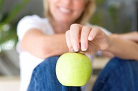 Woman holding green apple, smiling, portrait, close-up focus on apple