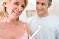 Couple standing in bathroom, woman holding up toothbrush, smiling, portrait