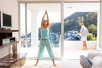 Woman stretching arms in bedroom, man on balcony in background
