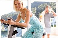 Mature woman riding stationary bicycle indoors, man smiling on balcony in background