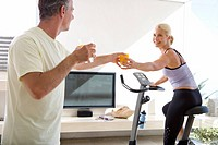 Mature man passing glass of juice to mature woman riding stationary bicycle in living room
