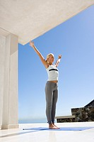 Mature woman standing on exercise mat outdoors, arms outstretched, low angle view