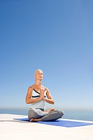 Mature woman meditating on exercise mat outdoors, eyes closed, sea in background