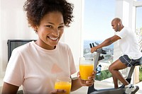 Woman holding glass of juice, smiling, portrait, man on stationary bicycle in background