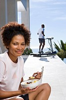 Woman sitting outdoors with bowl of cereal, smiling, portrait, man on running machine in background
