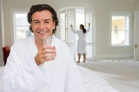 Man wearing white bath robe on bed, holding glass of water, woman standing in background