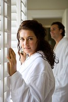 Couple wearing white bath robes, standing by window shutters, portrait of woman in foreground