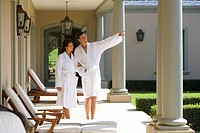 Couple wearing white robes, standing on verandah, man pointing