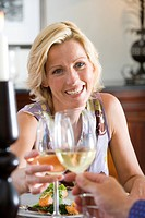 Friends toasting wine glasses over lunch table, woman smiling, close-up