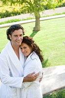 Couple wearing white robes, embracing outdoors, smiling, portrait