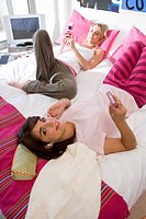 Two teenage girls 15-17 lying on bed, holding mobile phones, elevated view