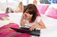 Two teenage girls 15-17 lying on bed, girl using laptop and mobile phone in foreground, smiling