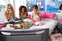 Three teenage girls 15-17 sitting on bed eating pizza, portrait