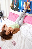 Teenage girl 15-17 lying on bed, talking on mobile phone, smiling, elevated view