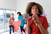 Three teenage girls 15-17 in bedroom, girl applying make-up in foreground