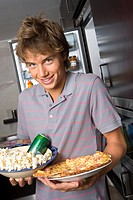 Young man holding popcorn and pizza, smiling, portrait, close-up