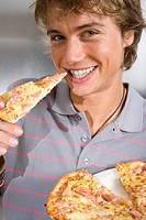 Young man eating pizza, smiling, portrait, close-up