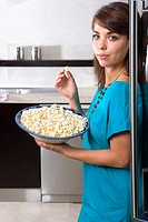 Young woman standing by fridge with bowl of popcorn, smiling, portrait