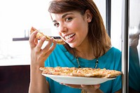 Young woman eating pizza, smiling, portrait, close-up