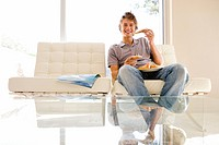 Teenage boy 16-18 sitting on sofa eating pizza, smiling, portrait