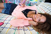 Teenage girl 16-18 lying on bed wearing earphones and holding mp3 player, smiling, portrait, close-up