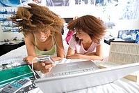 Two teenage girls 16-18 lying on bed with laptop, one holding mp3 player, shaking heads blurred motion