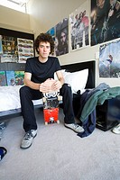 Teenage boy 16-18 sitting in bedroom with skateboard, portrait