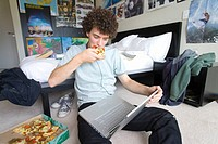 Teenage boy 16-18 sitting on bedroom floor with laptop and pizza